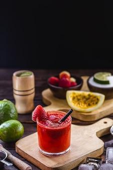 Copo de caipirinha, bebida típica do brasil, feita com morango, em mesa de madeira rústica