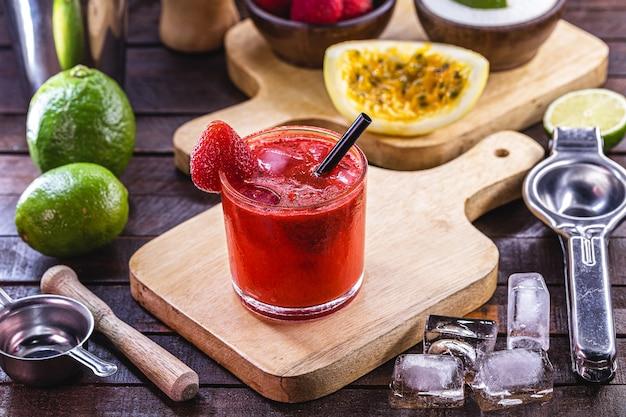 Copo de caipirinha, bebida típica do brasil, feito com morango, sobre fundo rústico de madeira
