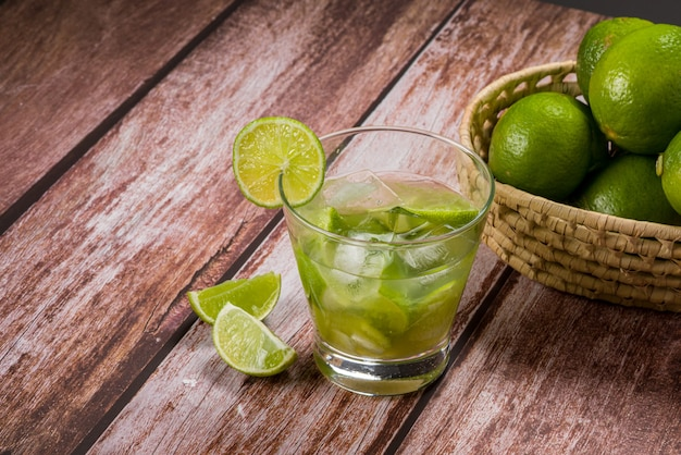 Copo de caipirinha com limão em mesa de madeira envelhecida bebida típica brasileira