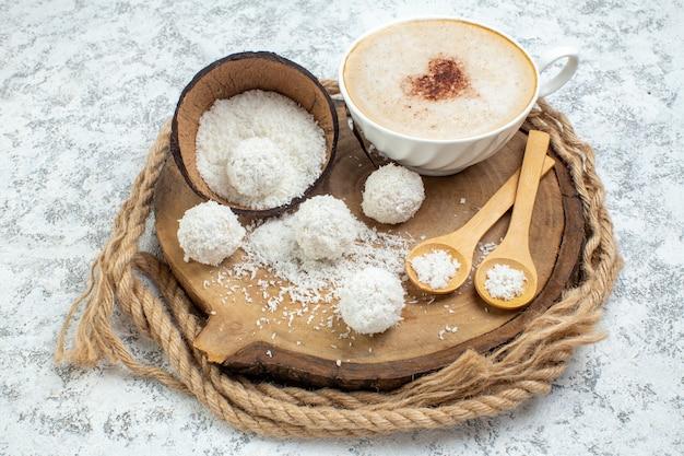 Copo de cappuccino com vista inferior e colheres de madeira em pó de coco na placa de madeira no fundo cinza