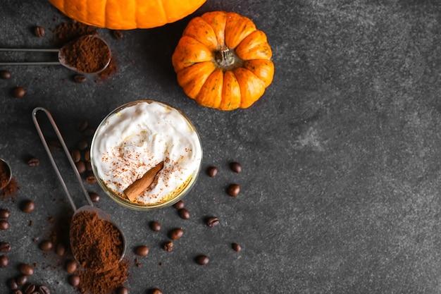 Copo de cappuccino de abóbora em superfície escura