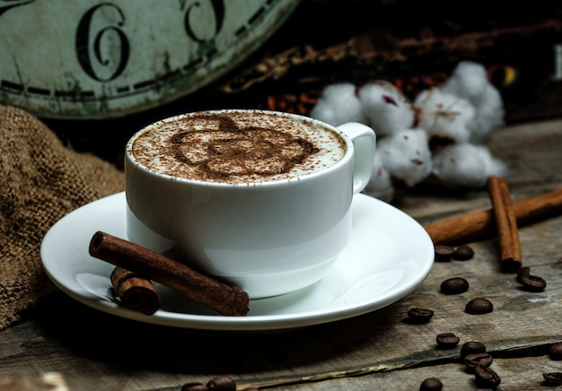Copo de cappuccino quente com padrão de canela