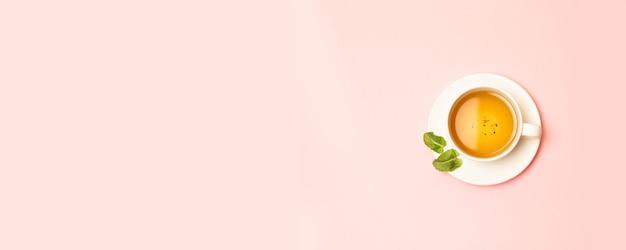 Copo de cerâmica branca com chá verde ou preto à base de plantas com folhas de hortelã