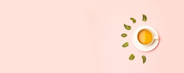 Copo de cerâmica branca com chá verde ou preto herbal com folhas de hortelã em rosa