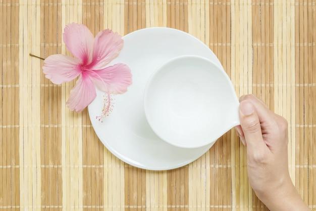 Copo de cerâmica branco closeup para bebidas com mão de mulher no fundo texturizado esteira de madeira turva