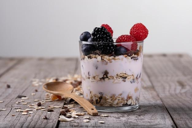 Copo de cereal com frutas da floresta, sobre uma base de madeira. conceito de café da manhã saudável