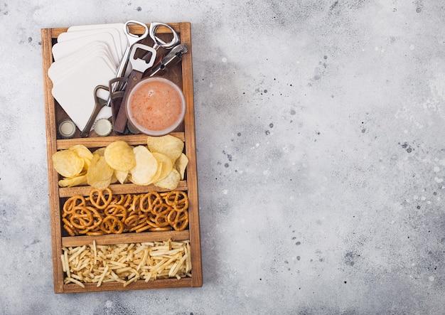 Copo de cerveja artesanal em caixa vintage de abridores de lanches e tapetes de cerveja na mesa da mesa da cozinha leve. pretzel, batatas fritas e batata salgada.