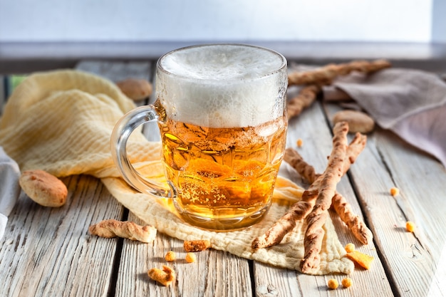 Copo de cerveja artesanal em caneca caneca de cerveja e salgadinhos pretzel