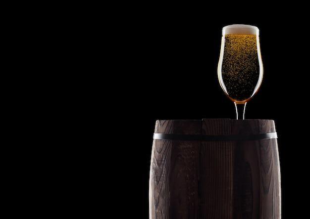 Copo de cerveja artesanal no barril de madeira velho em fundo preto com orvalho e bolhas. com espaço para o seu texto.