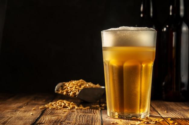 Copo de cerveja caseira em uma mesa de madeira. copo de cerveja artesanal em um fundo escuro.