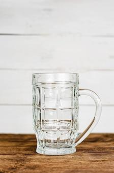 Copo de cerveja clara vazio, caneca na mesa de madeira. vertical, espaço para texto