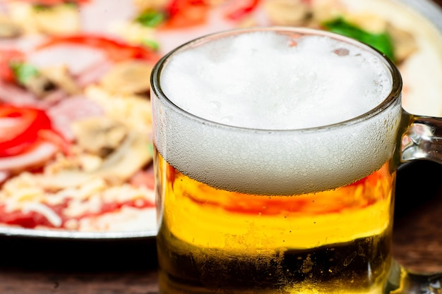 Copo de cerveja close-up no fundo da pizza.