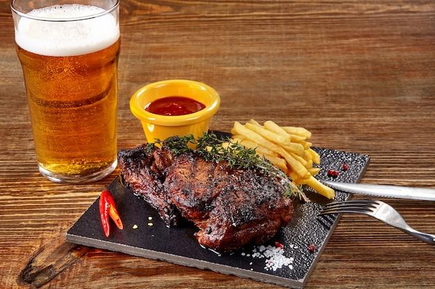 Copo de cerveja com bife gourmet e batatas fritas em fundo de madeira