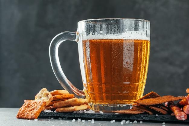 Copo de cerveja com bretzel e salsichas secas lanches close-up