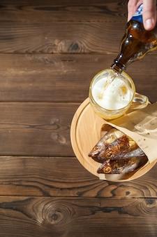 Copo de cerveja com cerveja e close-up de peixe defumado quente. caneca de cerveja com cerveja e peixe em um fundo escuro e copie o espaço.