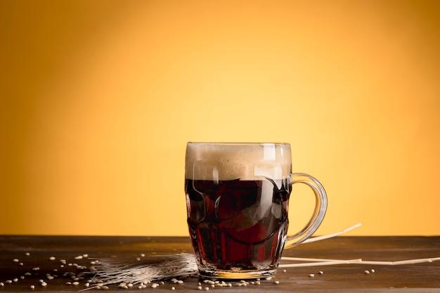 Copo de cerveja com cevada de espiga na mesa de madeira