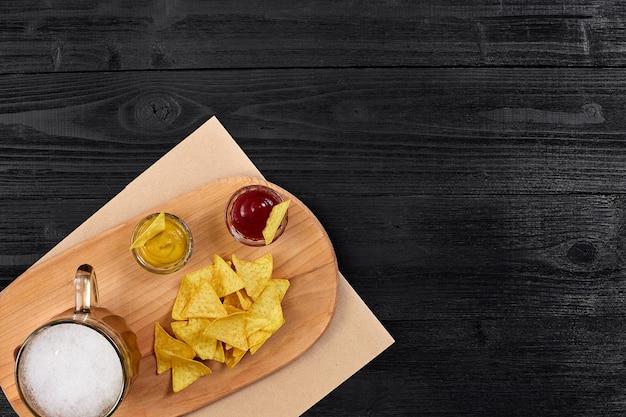 Copo de cerveja com chips de nachos em um fundo de madeira