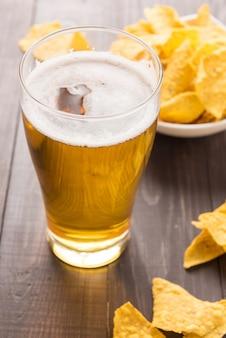 Copo de cerveja com chips de nachos em uma mesa de madeira