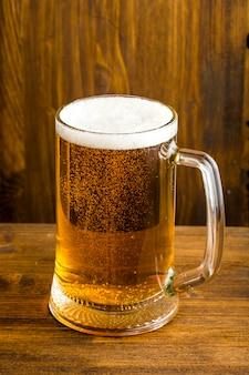 Copo de cerveja com espuma depositada na mesa de madeira