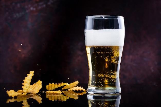 Copo de cerveja com espuma e batatas fritas em um fundo escuro