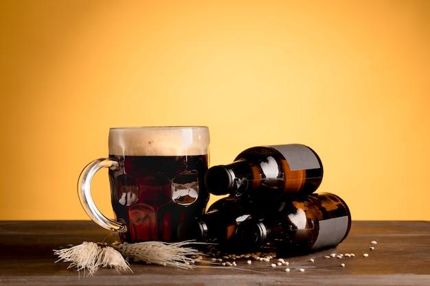 Copo de cerveja com espuma e garrafas de cerveja na mesa de madeira