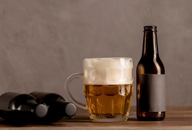 Copo de cerveja com espuma e garrafas marrons de cerveja na mesa de madeira