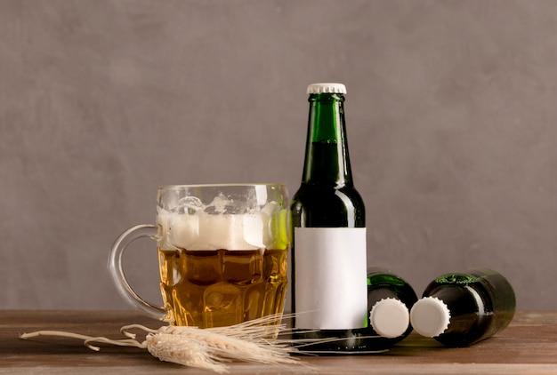 Copo de cerveja com espuma e garrafas verdes de cerveja na mesa de madeira