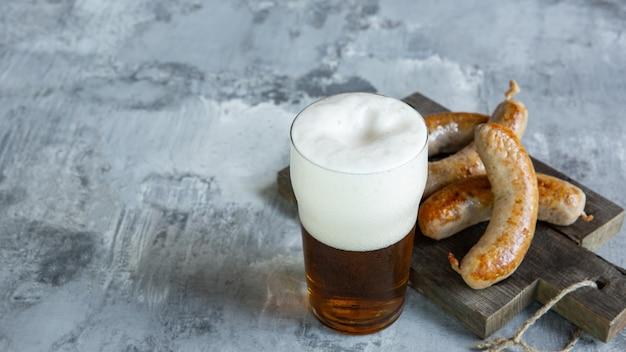 Copo de cerveja com espuma em cima da mesa de pedra branca.