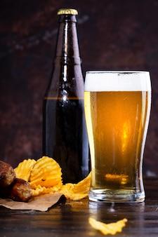 Copo de cerveja com espuma, salsichas fritas e batatas fritas em um fundo escuro