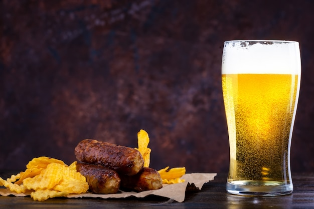 Copo de cerveja com espuma, salsichas fritas e batatas fritas no escuro