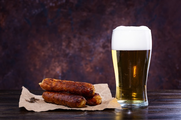 Copo de cerveja com espuma, salsichas fritas em um fundo escuro