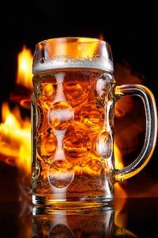 Copo de cerveja com fogo no fundo.