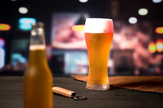 Copo de cerveja com garrafa desfocada