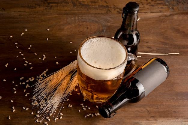 Copo de cerveja com garrafas marrons de cerveja na mesa de madeira