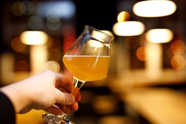 Copo de cerveja com uma perna fina na mão. fundo desfocado da barra