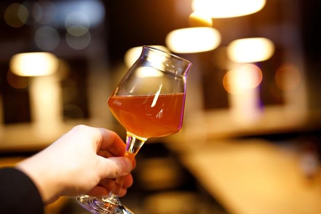 Copo de cerveja com uma perna fina na mão.
