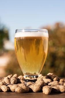 Copo de cerveja de baixo ângulo em cima de amendoins