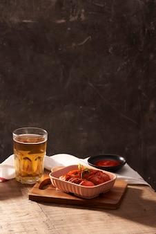 Copo de cerveja deliciosa com linguiça grelhada na mesa de madeira