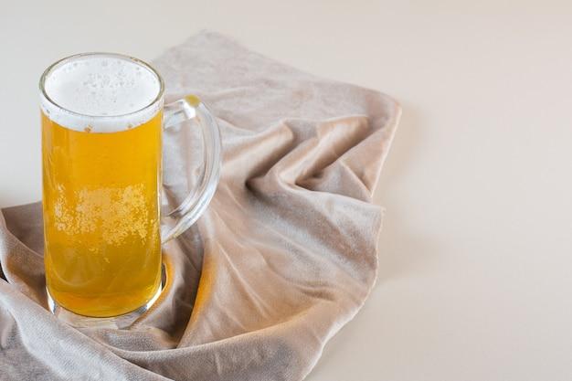 Copo de cerveja dourada gelada isolado em uma toalha de mesa leve