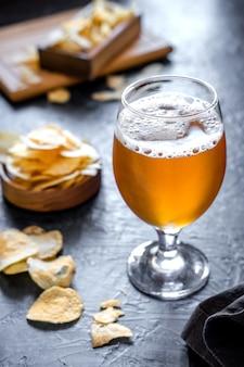 Copo de cerveja e batatas fritas em fundo escuro. cerveja gelada em copo comprido.