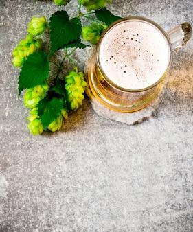 Copo de cerveja e lúpulo verde. na superfície da pedra.