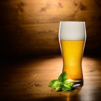 Copo de cerveja e pulo na madeira com espaço vazio