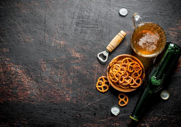 Copo de cerveja e salgadinhos pretzels na tigela. em fundo escuro rústico