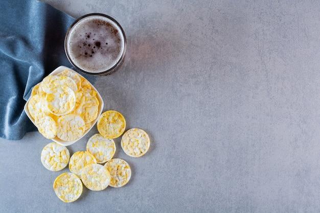 Copo de cerveja e tigela de batatas fritas em um pedaço de tecido, na superfície de mármore