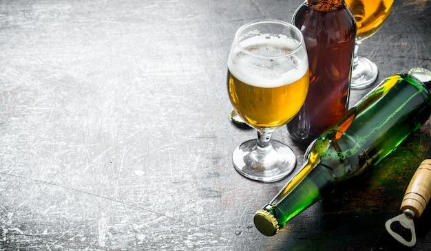 Copo de cerveja e uma garrafa. em fundo escuro rústico