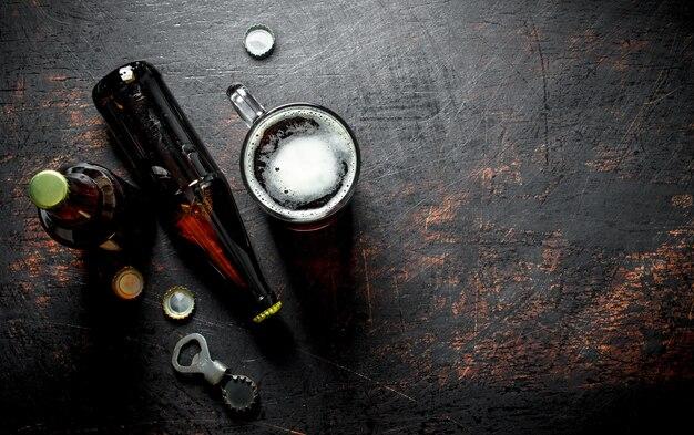 Copo de cerveja e uma garrafa. em fundo rústico