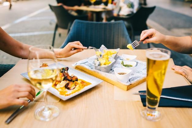 Copo de cerveja e vinho na mesa comendo comida no terraço - duas garotas almoçando juntas em um restaurante