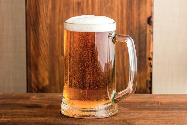 Copo de cerveja em cima de uma mesa de madeira