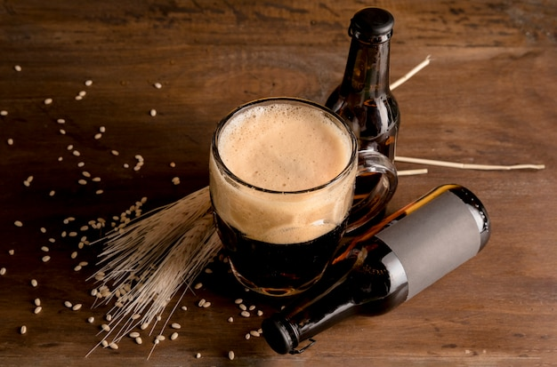 Copo de cerveja em espuma com garrafas marrons de cerveja na mesa de madeira