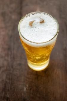 Copo de cerveja em fundo de madeira